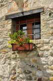 Window in a stone wall with flowers. Traditional architecture Stock Photos