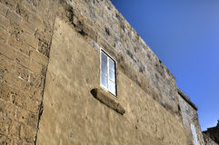 Window in a stone wall in one of the old streets in Mdina, historic Malta capital.  Stock Image