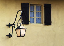 Window and street lamp. A detail of an old window with blue curtains near a street lamp Royalty Free Stock Photography