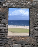 Window into Summer. Sharp edged window lined with rock looks out into the perfect beach Royalty Free Stock Photography