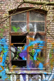 Window sundries. An old broken window with graffiti on a brick wall Stock Photo