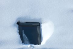 Window surrounded by snow in winter time. Reflecting window surrounded with white untouched snow Stock Image