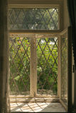 Window to the garden. Old vintage window with a grid. view from inside the house to the green garden Royalty Free Stock Image