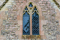 Window to an old English church. At the English churches are still preserved elements of the old knights time Royalty Free Stock Photography