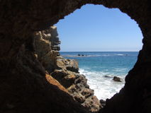 Window to the Sea. Peering through a natural window to the Pacific at Point Dume, Malibu, CA Stock Image