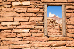 Window to Temple Mountain. A window through an old, partially collapsed building, left over from the days of heavy uranium mining, looks on at the craggy summit stock images