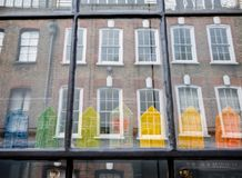 Window of traditional Huguenot weaver`s house on Princelet Street, Spitalfields, showing reflection and quirky model houses royalty free stock photography