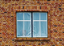 Window under the plastic film in brick wall Stock Image