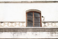 Window with video camera. Brown window with security video camera on renaissance wall Stock Images