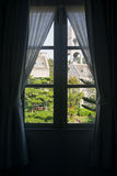 Window view of British style buildings. View of British style buildings on sunny day through closed window with curtains Royalty Free Stock Photography