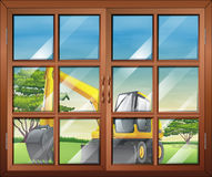 A window with a view of the bulldozer outside Stock Image