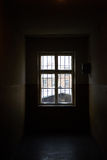 The window. View from the dark room to the light outside through the barred window Stock Image