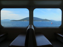 Window View from a Ferry. Beautiful and tranquil views of the ocean and a tree covered island from a Ferry sailing through the San Juan Islands, Puget Sound, in Stock Image