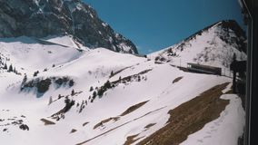 Window view of a Moving Mountain Train on the Snowy Switzerland Alps. Montreux City. Window view of a Moving Mountain Train on the Snowy Switzerland Alps. The stock footage
