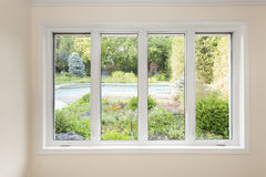 Window with view of summer backyard. Large four pane window looking on summer backyard with pool and garden stock image