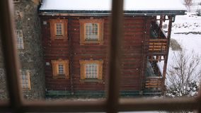 Through the window view of wooden cottage in mountain village during heavy snowfall. Snow falling on log chalets with. Stone chimney wall at ski resort. Cold stock video
