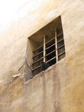 Window in the wall barred. The pigeon sits on the edge of the window of the old jail Royalty Free Stock Photography