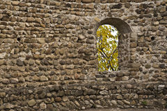 Window in a wall. Window in an old wall of a tower made of stone bricks stock images