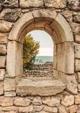 Window in the wall. The ruins of ancient Greek city of Chersonesus Taurica in the Crimea peninsula under the cloudy sky Royalty Free Stock Photo