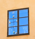 Window with reflection of blue sky and cross on yellow wall, Stockholm - Sweden - Scandinavia. Image assembled from few frames Stock Photos
