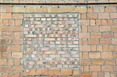 The window was walled up. Wall of red brick. The background Stock Photography