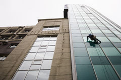 Window Washer. A window washer hangs from cables stock photography