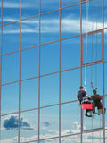 Window washer. At work and reflect the sky in the windows Royalty Free Stock Photo