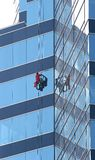 Window Washer on Blue Glass Stock Images