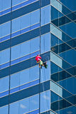 Window Washer in Orange Shirt on Blue Building Stock Images
