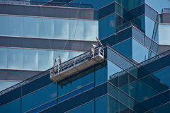 Window Washer Scaffold on Blue Angled Glass Stock Images