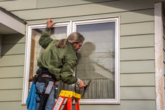 Window Washer Using Squeegee. Male window washer using a squeegee to remove a soapy solution from a window to clean the glass Stock Photo