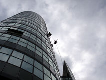 Window washers. Climbing and washing tower. In fact they are air performers who earn extra money by washing tower windows Stock Image