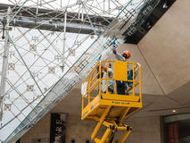 Window washers clean inverted pyramid in Carrousel du Louvre, Paris Royalty Free Stock Photography