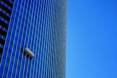 Window washers hanging off the side of a building just doing their job. Stock Photos