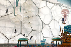 Window Washers inside the Water Cube. Workers hang from harnesses inside the Water Cube in Beijing's Olympic Park as they wash the windows inside the water park Royalty Free Stock Images