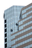 Window washers on skyscraper. Window washers hanging from skyscraper cleaning windows Royalty Free Stock Image
