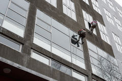 Window washers on top. Two workers hung ropes wash windows on high-rise Royalty Free Stock Images