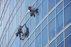 Window washers work on skyscraper, industrial alpinism. Window washers work on a skyscraper building, industrial alpinism Stock Photo