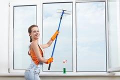 Window washing. The girl washing windows mop for washing windows Royalty Free Stock Photography