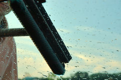Window Washing. Image of a man washing the windshield of his car. Shows the sky in the background and water beads on the windshield royalty free stock image