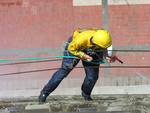 Window washing, extreme jobs. Window washing extreme work hanging on ropes. Man with mountain climbing equipment washing office building exterior Stock Photo