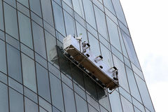 Window washing platform suspended on glass facade of a skyscraper royalty free stock images