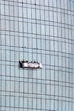 Window washing workers in the platform suspended on glass facade royalty free stock image