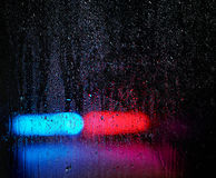 Window and water drops, emergency lights on background Royalty Free Stock Photo
