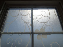 Window with white filigree and sun rays. Stock Images