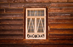 Window in a white frame on an old wooden wall. Toned Stock Image