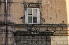 Window with white shutters in a very old house. House in emergency condition. Facade with cracks and holes needs repair Stock Photos