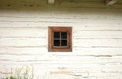Window on white wooden wall painted with lime. An old log house rustic village stock photography