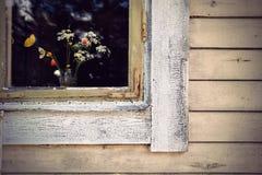 Window with wild flowers Royalty Free Stock Photos