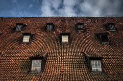 Symmetrical roof windows. Red tile. Seven windows on blue sky background. Royalty Free Stock Image